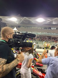 A camera operator filming next to a F1 racing circuit against dark skies in the evening