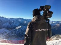 A man from behind, dressed in a Kuitu Media winter jacket holding a camera facing the Alps and blue skies